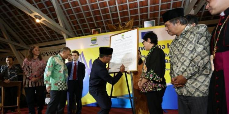 Wali Kota Bandung Ridwan Kamil saat menandatangani piagam HAM Kota Bandung di Pendopo Kota Bandung, Kamis (10/12/2015) malam. sumber foto: kompas.com